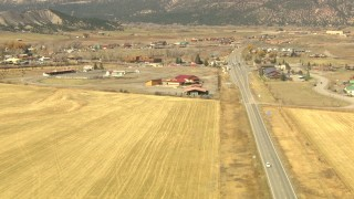 HDA13_349_01 - HD stock footage aerial video pan across a country highway to reveal the town of Ridgway, Colorado