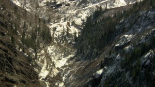 HDA13_353 - HD stock footage aerial video tilt from snowy mountains to canyon and mountain road, Rocky Mountains, Colorado