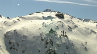 HDA13_355_02 - HD stock footage aerial video tilt from snowy slopes to a mountain summit in the Rocky Mountains, Colorado