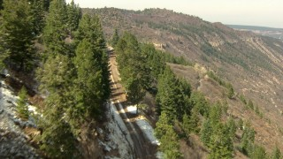 HDA13_383 - HD stock footage aerial video follow a mountain road to a fork in the Rocky Mountains, Colorado