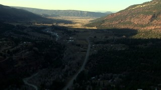 HDA13_392 - HD stock footage aerial video of following the highway at sunset toward rural homes in Ridgway, Colorado