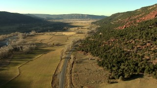 HDA13_394 - HD stock footage aerial video of following the highway past fields toward the town of Ridgway, Colorado