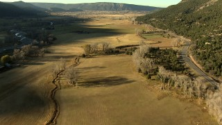 HDA13_395_01 - HD stock footage aerial video of tilting from highway and fields while approaching Ridgway, Colorado at sunset