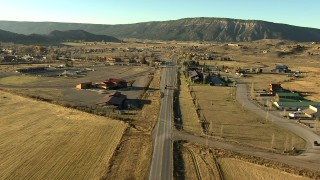HDA13_395_02 - HD stock footage aerial video of flying over fields and grazing animals on the way to Ridgway, Colorado at sunset