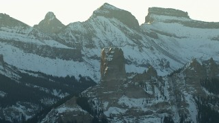 HDA13_403_03 - HD stock footage aerial video of snowy Rocky Mountains and a rock formation at sunrise, Colorado