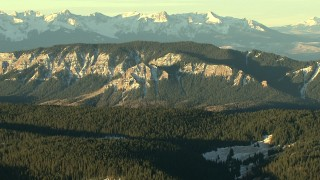 HDA13_408 - HD stock footage aerial video of a reverse view of mountain ridges with snow at sunrise, Rocky Mountains, Colorado