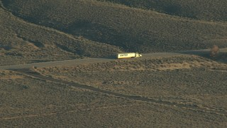 HDA13_418 - HD stock footage aerial video of a big rig on Highway 50 at sunrise, Blue Mesa Reservoir, Colorado