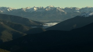 HDA13_438_02 - HD stock footage aerial video of fog between mountain slopes near snowy Rocky Mountains at sunrise, Colorado