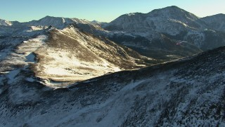 HDA13_445 - HD stock footage aerial video approach and fly over ridges with snow in the Rocky Mountains at sunrise, Colorado