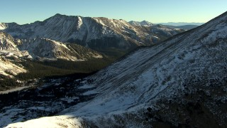 HDA13_447 - HD stock footage aerial video of flying over a snowy mountain slope at sunrise, Rocky Mountains, Colorado