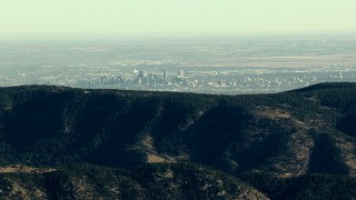 HDA13_480 - HD stock footage aerial video of the Denver skyline seen from a green ridge in the Rocky Mountains, Colorado