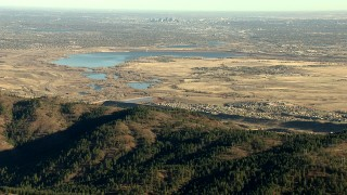 HDA13_482_06 - HD stock footage aerial video zoom to wider view of Downtown Denver and reservoir, reveal Roxborough Park, Colorado