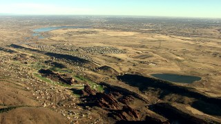 HDA13_483_01 - HD stock footage aerial video of Roxborough Park and reservoirs, zoom tighter on Downtown Denver skyline, Colorado