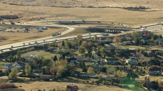 HDA13_486_02 - HD stock footage aerial video of a freeway interchange beside a suburban neighborhood in Castle Pines, Colorado