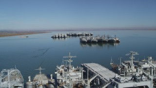 JDC01_041 - 5K stock footage aerial video tilt from Suisun Bay, reveal National Defense Reserve Fleet warships, Suisun Bay, California