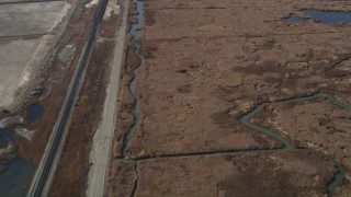 JDC01_058 - 5K stock footage aerial video of flying away from railroad tracks, country road beside marshlands, Martinez, California