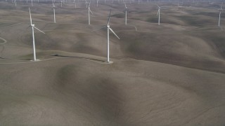 JDC01_063 - 5K stock footage aerial video tilt from small hills, reveal Shiloh Wind Power Plant windmills, Montezuma Hills, California
