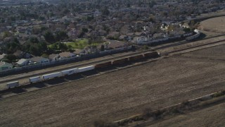 JDC01_084 - 5K stock footage aerial video of tracking train traveling by suburban area, fields, Pittsburg, California