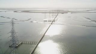 JDC03_009 - 5K stock footage aerial video of flying over marshland, tilt up, revealing power lines, Sunnyvale, California