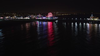 LD01_0039 - 5K stock footage aerial video tilt from the ocean to reveal Santa Monica Pier, California at night