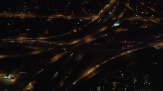 LD01_0047 - 5K stock footage aerial video orbit of a freeway interchange at night in West Los Angeles, California