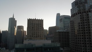 PP0002_000082 - 5.7K stock footage aerial video descend by skyscrapers at sunrise, reveal office building, Downtown San Francisco, California
