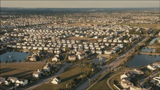 PP001_003 - HD stock footage aerial video of flying by suburban tract homes at sunset in Joliet, Illinois
