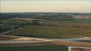 PP001_006 - HD stock footage aerial video of flying over freeway and farm fields at sunset in Homer Glen, Illinois