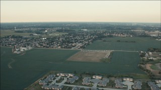 PP001_008 - HD stock footage aerial video of flying over fields to approach homes at sunset in Homer Glen, Illinois