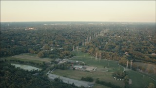 PP001_012 - HD stock footage aerial video of fly over barns to approach power lines and homes at sunset in Orland Park, Illinois