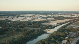 PP001_014 - HD stock footage aerial video approach warehouses across the river with a bridge at sunset in Alsip, Illinois