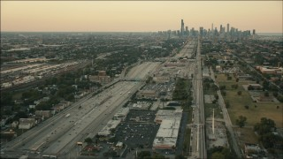 PP001_020 - HD stock footage aerial video follow freeway and rail through South Side at sunset toward Downtown Chicago, Illinois
