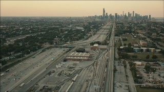 PP001_021 - HD stock footage aerial video fly over train yard by freeway to approach Downtown Chicago, Illinois at sunset