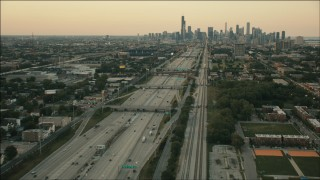 PP001_022 - HD stock footage aerial video of following freeway and train tracks at sunset to approach Downtown Chicago, Illinois