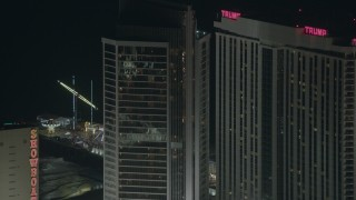 PP003_036 - HD stock footage aerial video of flying by a hotel and casino to reveal rides on Steel Pier at night, Atlantic City, New Jersey