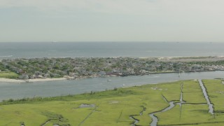 PP003_049 - HD stock footage aerial video of a coastal community across a channel and marshes, Point Lookout, New York