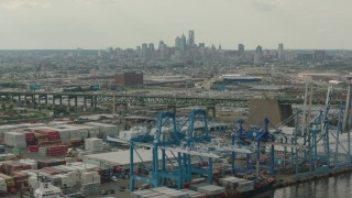PP003_091 - HD stock footage aerial video of containers and cranes at a shipping port, with a view of Downtown Philadelphia skyline, Pennsylvania