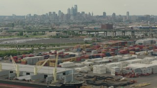 PP003_092 - HD stock footage aerial video of the Downtown Philadelphia skyline seen while passing containers at a shipping port, Pennsylvania