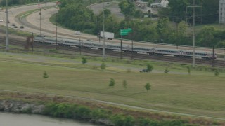 PP003_107 - HD stock footage aerial video of a commuter train by a freeway in Wilmington, Delaware