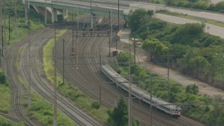PP003_108 - HD stock footage aerial video track a commuter train approaching an overpass in Wilmington, Delaware