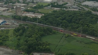 PP003_110 - HD stock footage aerial video of a passenger train passing industrial buildings in Wilmington, Delaware