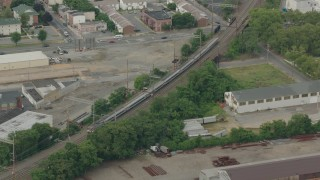 PP003_114 - HD stock footage aerial video track a commuter train passing industrial buildings in Wilmington, Delaware
