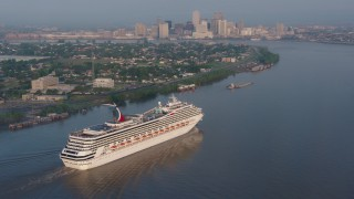 PVED01_013 - 4K stock footage aerial video of Carnival Cruise ship sailing Mississippi River, reveal Downtown New Orleans at sunrise, Louisiana