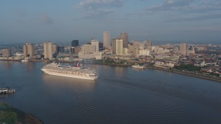 PVED01_031 - 4K stock footage aerial video of a Carnival Cruise ship on the river by Downtown New Orleans at sunrise, Louisiana