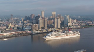 PVED01_037 - 4K stock footage aerial video orbit a Carnival Cruise ship sailing by Downtown New Orleans at sunrise, Louisiana
