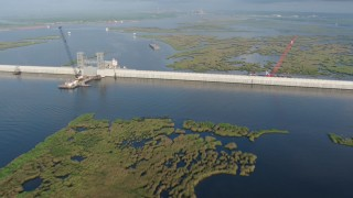 PVED01_076 - 4K stock footage aerial video pan across surge barrier and orbit a gate at sunrise in St. Bernard Parish bayou, Louisiana