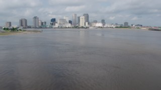 PVED01_129 - 4K stock footage aerial video tilt to reveal Downtown New Orleans skyline while flying over Mississippi River, Louisiana