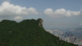 SS01_0001 - 5K stock footage aerial video approach rocky summit with apartment buildings in distance in Kowloon, Hong Kong