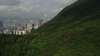 SS01_0034 - 5K stock footage aerial video fly over forest mountain and tilt to reveal skyscrapers on Hong Kong Island, China