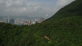 SS01_0038 - 5K stock footage aerial video fly over forest and mountain to reveal skyscrapers on Hong Kong Island, China